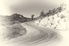 Road in French Alps. Winding Asphalt Road in the French Alps, Stylized Photo Royalty Free Stock Image