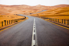 Winding black asphalt road through the sand dunes of Liwa oasis, United Arab Emirates Stock Images