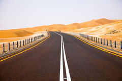 Winding black asphalt road through the sand dunes of Liwa oasis, United Arab Emirates Stock Photography