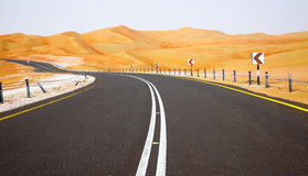 Winding black asphalt road through the sand dunes of Liwa oasis, United Arab Emirates Royalty Free Stock Photos