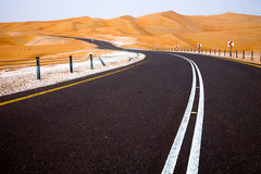 Winding black asphalt road through the sand dunes of Liwa oasis, United Arab Emirates Royalty Free Stock Images