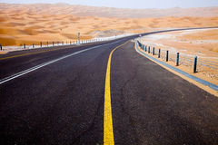 Winding black asphalt road through the sand dunes of Liwa oasis, United Arab Emirates Royalty Free Stock Image