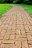 A winding brick path among green grass with green landscaping in the background. This is a view of a winding brick walk path in a luscious green lawn nestled Royalty Free Stock Images