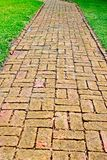 A winding brick path among green grass with green landscaping in the background. This is a view of a winding brick walk path in a luscious green lawn nestled Stock Photo