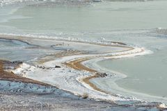 The winding coast of the frozen sea with sand and ice on land. Stock Photos