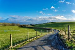 A winding country lane passing through green fields. Royalty Free Stock Photos