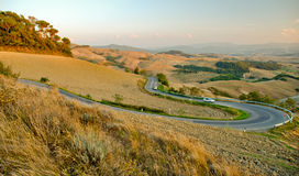 Winding Country Road. A twisty country road winding its way through the Tuscan countryside towards the hilltop town of Volterra royalty free stock images