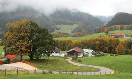 A winding country road curves between green fields and autumn trees leading to a farmhouse on a beautiful hillside Stock Photography