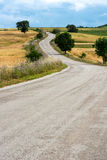 Winding country road leading to low hills Stock Photo