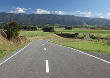 Winding Country Road, New Zealand. Country road winding through lush farmland, New Zealand Royalty Free Stock Photo