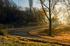 Winding countryside road in late autumn fog. Dangerous turnaround on serpentine in mountains Royalty Free Stock Photos