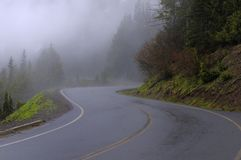 Winding curve road in a foggy forest stock photos