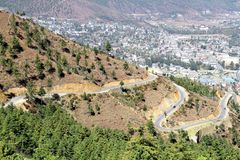 Winding or curved asphalt road on the hill with view of Thimphu royalty free stock photos
