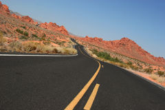 Winding desert road. And red rocks stock photos
