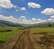 Winding dirt road. And cloudscape Royalty Free Stock Photography