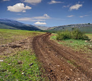 Winding dirt road. And cloudscape Stock Image