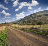 Winding dirt road. And cloudscpe Stock Photos