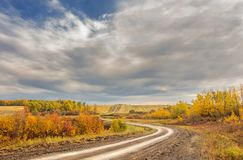 Winding dirt road in autumn landscape. A narrow dirt road winding through autumn colored foliage between harvest ready fields in a cloudy morning countryside Royalty Free Stock Photo