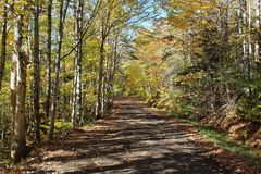 A winding dirt road through the hills of Cape Breton on a fall day in a remote rural area. A rural scene on Cape Breton Island at a remote location along the royalty free stock photo