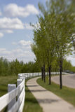 Winding fence. White picket fence winding along a sidewalk & road, with green trees & clouds Stock Photo