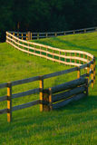 Winding Fence In flower filled meadow. A long wooden fence winds through a grass and flower filled farm field stock photography