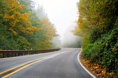 Winding highway autumn road disappearing into the fog. Winding autumn highway with two lanes and a dividing strip and metal fencing for security passes royalty free stock photography