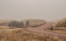 Winding highway in the fog. Winding highway over a hill in the fog Royalty Free Stock Images