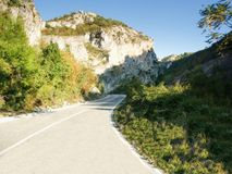 Winding highway through a large mountain. During a sunny day stock photos