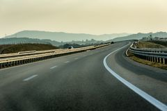 Winding Highway through Rural Landscape. With few cars on a cloudy Overcast Day royalty free stock photography