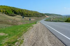 A winding highway stretching into the distance against the backdrop of a beautiful spring landscape, fields, meadows, forests and. Hills. Road stripes on royalty free stock photo