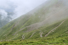 Winding hiking route on green slope Royalty Free Stock Photos