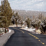 Winding into the hills. A country back road in Central Oregon winds through juniper trees with unexpected fresh snow and on to the hills on a spring day royalty free stock photos