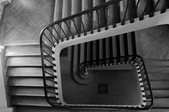 Winding interior staircase with bannister. Rails in a rectangular stairwell viewed from the top looking down to the ground floor royalty free stock image