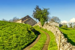 Winding lane leading uphill to a barn. A winding lane leading uphill to a barn with a dry stone wall stock photo