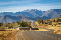 Winding Lesotho Road. A winding road leads through a village to the mountains in rural Lesotho royalty free stock image