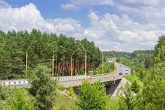 Motorway with forest on both sides and bridge on foreground. Winding motorway at a slope with forest on both sides and bridge on a foreground in summer day stock photos