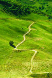 A winding mountain path surrounded by green grass. Straight roads must be illegal in this valley Royalty Free Stock Photos