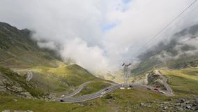 Winding Mountain Road on Mountainside. Summer mountainside landscape with winding mountain road and clouds. View from Transfagarasan road (Romania stock footage
