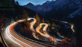 Winding road of Maloja Pass in Switzerland. The winding mountain road at the night with light tracks from cars, Maloja Pass, Switzerland Royalty Free Stock Photos