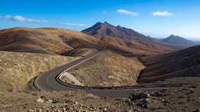 Winding mountain road. Mountain road, winding between the red coloured mountains Stock Image