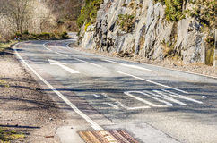 Winding Mountain Road and Warning Signs on Tarmac Stock Photos
