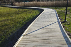 Winding new  wooden path walkway in park Royalty Free Stock Photos