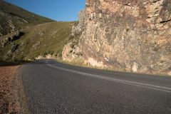 Winding open tar road landscape. Winding open tar roads in between dry land and mountains in Africa Royalty Free Stock Photography