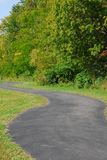 Winding Path 2. A blacktop path winding through a grassy park royalty free stock image