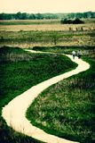 Winding path. Through grass prairie with two people walking along it Royalty Free Stock Photography