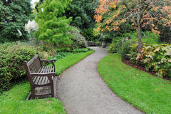 Winding Path in a Green Park. Winding Pathway and Wooden Bench in a Peaceful Green London Park Royalty Free Stock Images