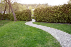 Winding path through the landscaped summer park. Green park outdoor Royalty Free Stock Photography