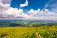 Path through the mountain ridge. Winding path through large meadows on the hillside of Carpathian mountain ridge Stock Images