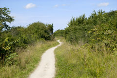 Winding path under a blue cloudy sky Stock Photography