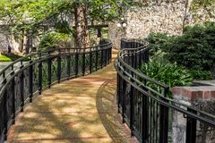 Winding pathway on the riverwalk on a sunny day. Winding pathway with decorative metal handrails on the river walk in San Antonio Texas on a sunny summer day royalty free stock image